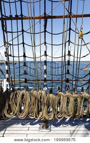 Many brownish thick ropes bend together in a sailing ship