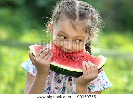 Beautiful Kid Girl Eating Big Red Watermelon On Summer Day Green Glass Background. Closeup Potrait