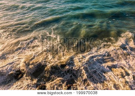 View on a wild Sea in Sunlight. Close-up of crashing Waves. Natural Background. Power in Nature