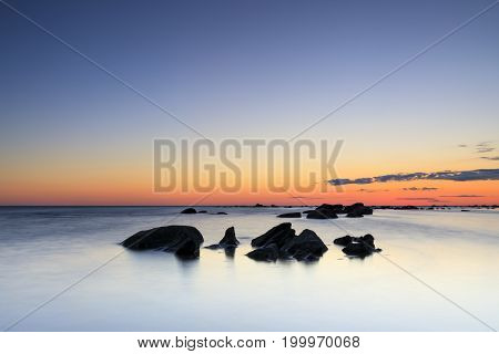 Several rocks in calm sea at summer sunset