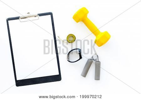 Fitness for loosing weight. Dumbbells, expander and measure tape on white background top view.