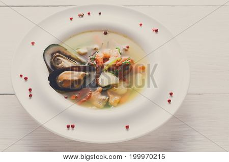 French cuisine restaurant. Seafood soup with white fish, shrimps and mussels in plate sprinkled with spices. Freshly cooked exclusive meals at wooden background with copy space