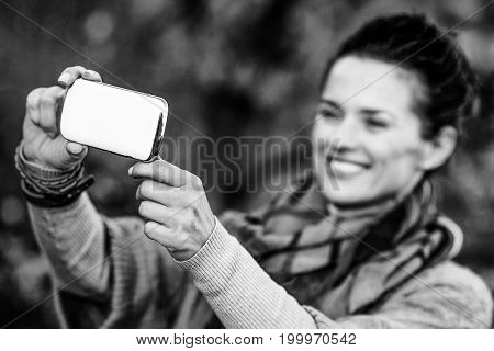 Closeup On Young Woman In Autumn Evening Outdoors Taking Photo W