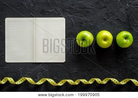 Slimming diet dairy. Notebook, apples and measuring tape on black background top view.