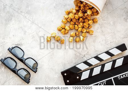 Watching film. Clapperboard, glasses and popcorn on grey background top view.