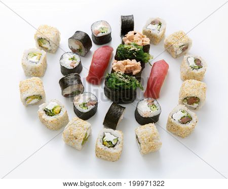 Big party sushi set isolated on white background. Japanese food delivery and take away. Fish and vegetable rolls, tuna nigiri, spicy gunkans with seaweed