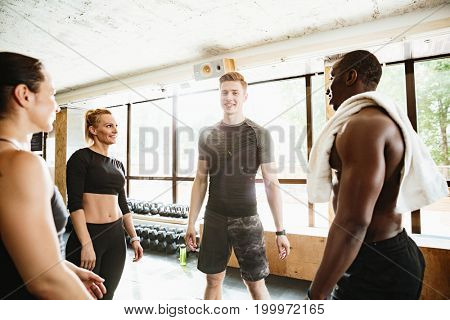 Picture of group of sports strong people standing in gym. Looking aside.
