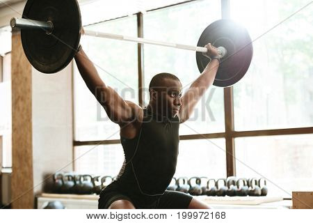 Strong muscular african sportsman lifting a barbell at the gym