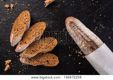 French homemade baguette bread. Rye baguette on black shale. cut baguette, top view.