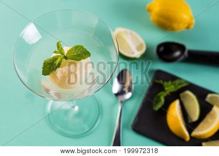 Lemon sorbet garnished with mint leaf. Tasty sorbet in high glass with spoon. Citrus ice-cream with lemon and lime on Turquoise background.