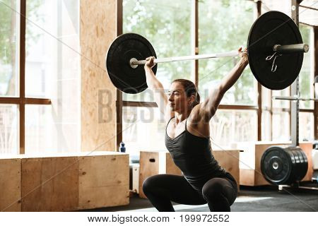 Sporty concentrated woman exercising with barbell in a gym
