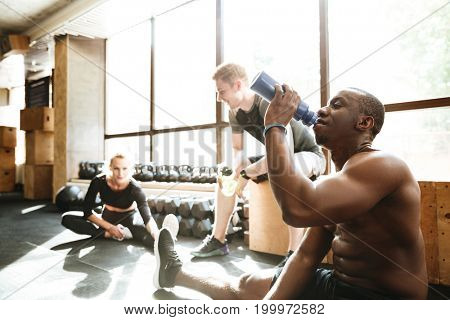 Picture of group of sports strong people sitting in gym. Looking aside drinking water.