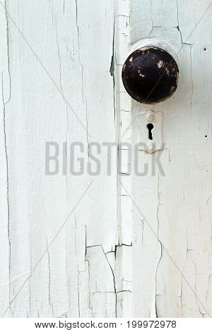 White painted and peeling vintage door and door knob with key hole.