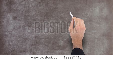 Hand of a businessman writing with a white chalk against empty blackboard in school