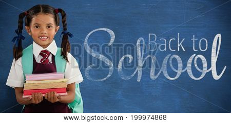 Smiling schoolgirl carrying books against blue background