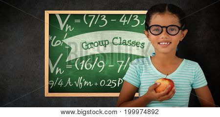 Portrait of smiling girl wearing eyeglasses holding apple against group classes against green chalkboard
