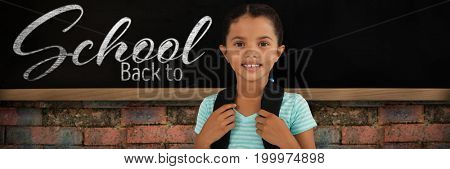 Portrait of smiling girl with bag against blackboard on brick wall