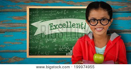 Happy girl holding books and apple against excellent! against green chalkboard