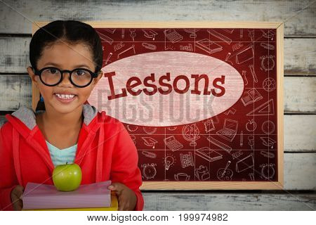 Happy girl holding books and apple against lessons against desk