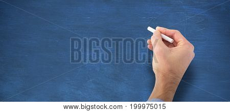 Hand writing with a white chalk against blue background