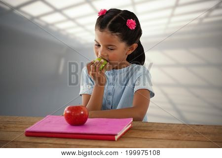 Girl eating Granny Smith apple at table against white room with windows at ceiling