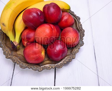 Ripe yellow bananas and red peaches on a copper plate