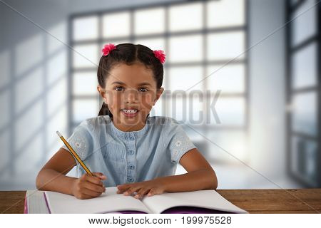 Smiling girl writing in book at desk against room with large windows showing city