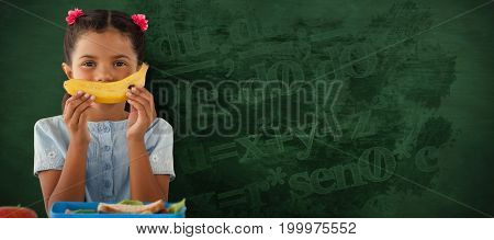Girl holding banana at table against green background
