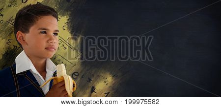 Schoolboy looking away while eating banana against black background