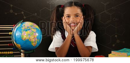 Schoolgirl leaning by globe and books against blackboard