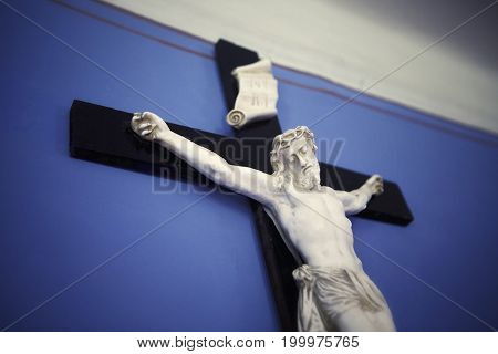 wooden cross with Jesus on a blue wall