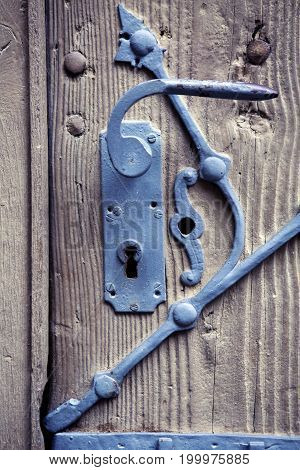 closeup of old rustic door handle with iron and wood