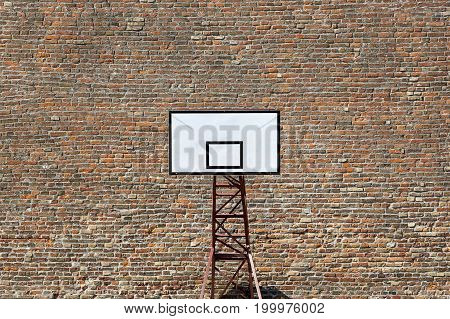 Basketball shield on a sports field on a brick wall background