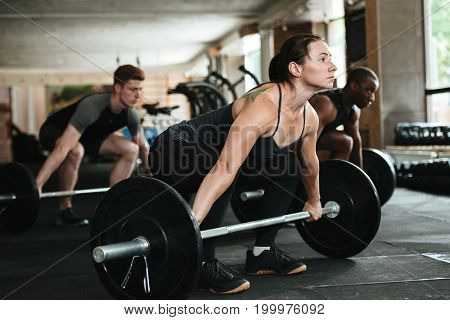 Group of multiracial young people exercising with barbells together at the gym
