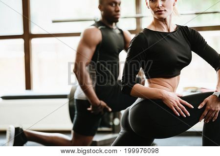 Cropped image of group of sports strong people in gym make sports exercises