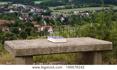 book on a stone bench with view of a small geman town