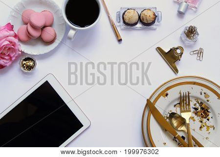 Modern styled desk top with wedding planner supplies. Sweets, coffee, office and beauty supplies, tablet, and dinner ware. Copy space.