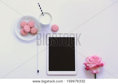 Modern styled desk top with macaroons, milk, rose and tablet. Copy space.
