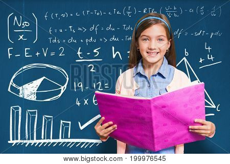 Portrait of girl holding pink book against blackboard with copy space on wooden board