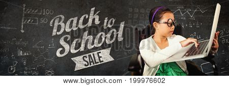 Young girl typing on laptop while sitting against close-up of blackboard