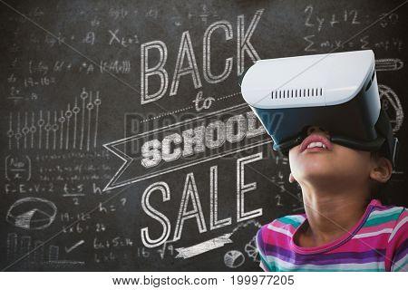 Close up of girl using virtual reality simulator against close-up of blackboard