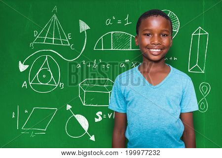 Portrait of smiling boy standing against blackboard with copy space on wooden board