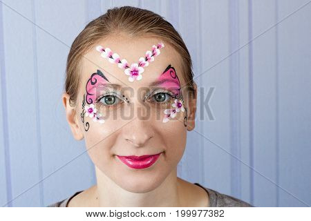 Young woman with face painting pink butterfly mask