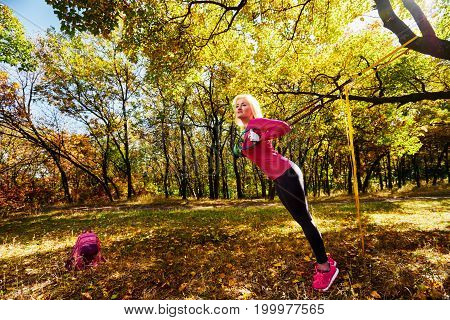Young woman exercising with suspension trainer in autumn park