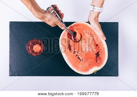 Female Hands Slices A Watermelon And Put The Pieces In A Glass On A White Table