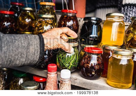 Wrinkled old women's hands hold a jar with homemade jam from coniferous leaves in the mountains