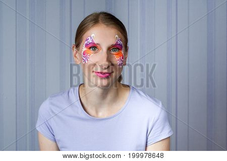 Young woman with face painting orange butterfly mask