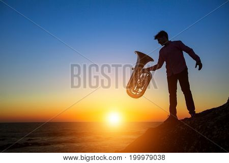 Silhouette of musician with the Tuba on rocky sea coast during sunset.