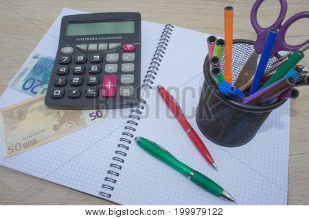 Photo shows a closeup of business calculator and money on a paper. Business Objects in the office on the table