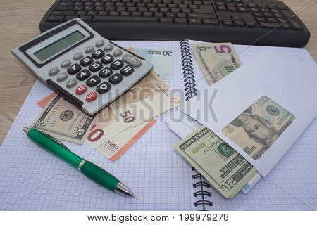 Business Objects in the office on the table calculator and dollars on table. Money and a calculator on the table